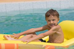 Happy child playing on the swimming pool at the day time. Royalty Free Stock Photos