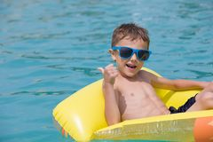 Happy child playing on the swimming pool at the day time. Royalty Free Stock Photo