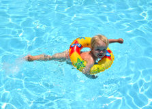 Happy child playing in swimming pool learning how to swim in Lif Royalty Free Stock Photo