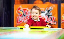 Happy child playing table air hockey Stock Images