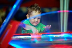 Happy child playing table air hockey at fair Stock Images