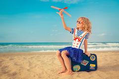 Happy child playing with toy airplane. Against sea and sky background. Kid pilot having fun outdoor. Summer vacation and travel concept. Freedom and imagination Royalty Free Stock Photos
