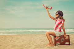 Happy child playing with toy airplane. Against sea and sky background. Kid pilot having fun outdoor. Summer vacation and travel concept. Freedom and imagination Stock Photos