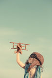 Happy child playing with toy airplane against summer sky. Background. Travel and adventure concept. Retro toned Stock Photo