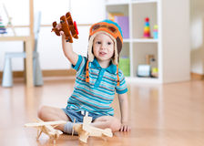 Happy child playing with toy airplane at home stock images