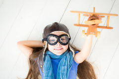 Happy child playing with toy airplane. Kid lying on wooden floor at home Stock Images