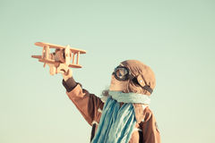 Happy child playing with toy airplane. Happy kid playing with toy wooden airplane against autumn sky background. Retro toned Royalty Free Stock Images
