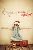 Happy child playing with toy airplane. Happy child in Santa Claus hat playing with toy airplane at home. Retro toned Stock Photo