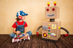 Happy child playing with toy robot Stock Photo