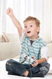 Happy child playing a video game. Happy child - little boy playing a video game Royalty Free Stock Photo