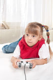 Happy child playing a video game. Happy child - little girl playing a video game Stock Photo