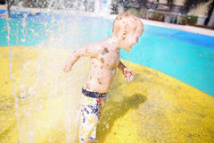 Happy Child Playing at Water Splash Park on Summer Day Royalty Free Stock Photo