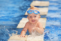 Happy child playing with water splashes in pool Stock Photos
