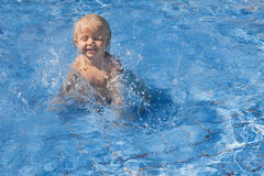 Happy child playing with water splashes in pool Royalty Free Stock Photography
