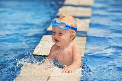 Happy child playing with water splashes in pool. Happy smiling baby with underwater goggles is having fun playing with splashes in blue water in pool before Royalty Free Stock Photo