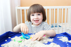 Happy child plays kinetic sand at home Stock Images