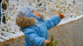 Happy child plays in a Park with snowy tree Royalty Free Stock Photo