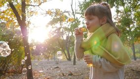 Happy child plays with soap bubbles in park in sunlight on nature stock footage