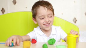 A happy child plays at the table with multicolored figures of plasticine or dough for games stock video