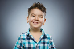 Happy child. Portrait of handsome boy smiling isolated on grey background royalty free stock image
