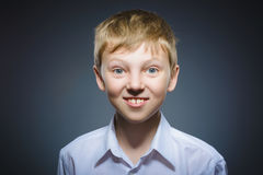 Happy child. Portrait of handsome boy smiling isolated on grey background royalty free stock photography