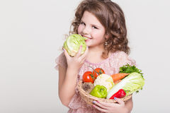 Happy child portrait with organic vegetables, little girl smiling, studio Royalty Free Stock Photo