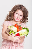 Happy child portrait with organic vegetables, little girl smiling, studio Stock Images