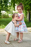 Happy child portrait, two girl love and embrace in city park, su Stock Photography