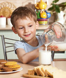 Happy child pours milk from jug Stock Photos