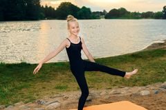 Happy child practicing yoga pilates on the river bank royalty free stock photo