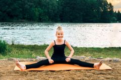 Happy child practicing yoga pilates on the river bank royalty free stock photos