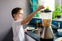 Happy child preparing fruit cocktail in kitchen. Mixing fruits in blender. Healthy eating royalty free stock image