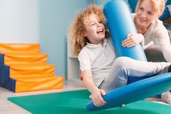Happy child and professional therapist. Professional therapist and happy child sitting on swing royalty free stock image