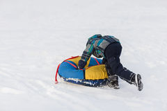 Happy child pushes the tubing in the snow in the winter frosty day stock photos
