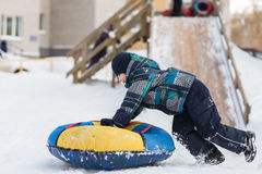 Happy child pushes the tubing in the snow in the winter frosty day Royalty Free Stock Photos