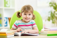 Happy child reading book at table in nursery Stock Photo