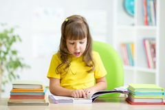 Happy child reading book at table in nursery Royalty Free Stock Images