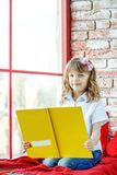 A happy child reads a book near the window. Conception childhood royalty free stock photography