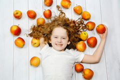 Happy child with red apples on light wooden floor. Top view. Stock Photos