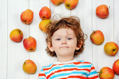 Happy child with red apples on light wooden floor. Top view. Royalty Free Stock Photo
