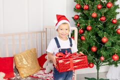 A happy child in a red hat holds a gift for new year or Christmas in the children`s room with a new year`s interior near the