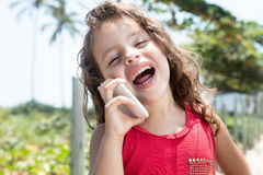 Happy child in a red shirt laughing at mobile phone outside. In the city Stock Photography