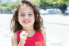 Happy child in a red shirt outside. In a park with green plants in the background Stock Photography