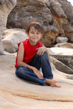 Happy child relaxes on rocks Royalty Free Stock Photo