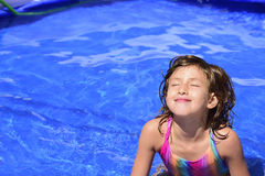 Happy child relaxing in the pool Stock Images