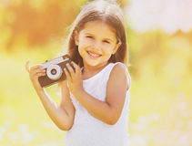 Happy child with retro camera having fun. Outdoors Royalty Free Stock Images