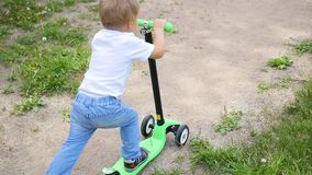 A happy child rides his scooter in the Park.Fun outdoors. A child rides his scooter in the Park stock footage