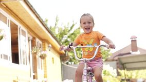 Happy child riding a bike. Girl on a bicycle. Сhildren summer activity.