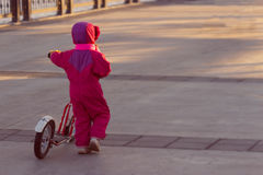 Happy child riding a bike. Little girl on a pink bicycle Stock Photos