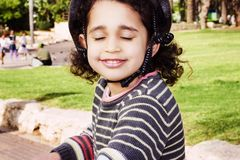 Happy child riding a bike in outdoor. Cute kid in safety helmet biking outdoors. Royalty Free Stock Photo